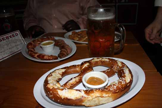 A feast of Oktoberfest goodies: pretzel, sausages, and of course - beer.