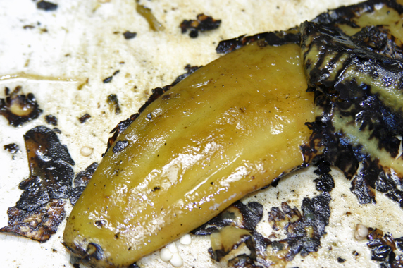 Close-up of a single chile as the skin is being removed